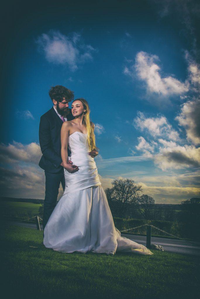 Bride and groom with OCF flash, blue sky Hazlewood Hall